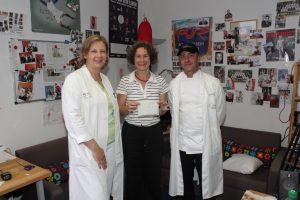 Foto der Spendenübergabe im RUMMS-Studio mit RUMMS-Redakteurin Stephanie und zwei Vertretern des UMM-Küchenteams
