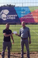 Bild der Spendenübergabe im Rahmen von Anpfiff ins Leben, zu sehehn sind Daniel Hecht und Martin Kerkmann